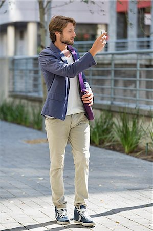 Man taking a picture with mobile phone on a street Stock Photo - Premium Royalty-Free, Code: 6108-06908143
