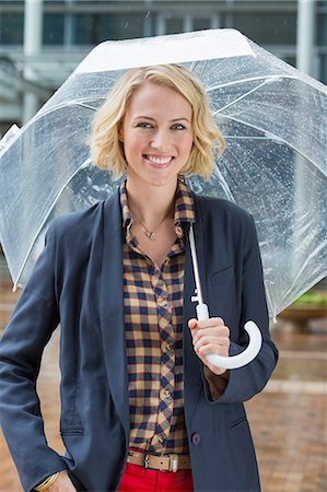 Portrait of a smiling woman with an umbrella Stock Photo - Premium Royalty-Free, Code: 6108-06908124