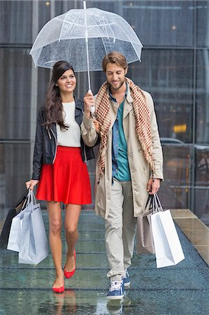 people with umbrellas in the rain - Couple with shopping bags sheltering under umbrella in rain Stock Photo - Premium Royalty-Free, Code: 6108-06908128