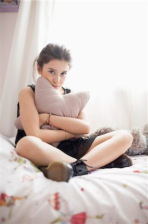 preteen beauty - Girl looking serious on the bed Stock Photo - Premium Royalty-Free, Code: 6108-07969515