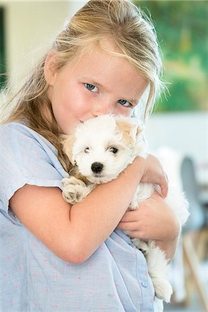 dog kissing girl - Portrait of a cute girl hugging a puppy Stock Photo - Premium Royalty-Free, Code: 6108-08662485