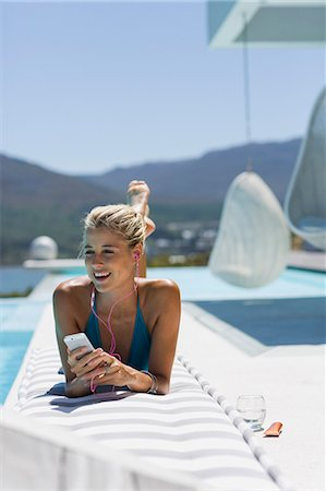 Young woman listening to music with smart phone at the poolside Stock Photo - Premium Royalty-Free, Code: 6108-08662585