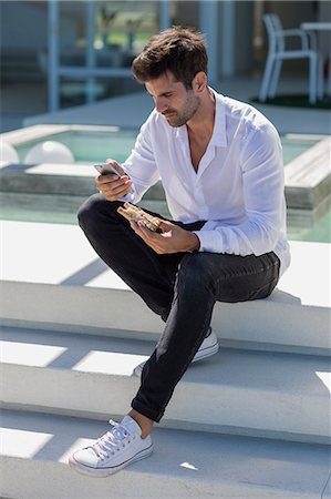Mid adult man using a smart phone and eating sandwich Stock Photo - Premium Royalty-Free, Code: 6108-08662601