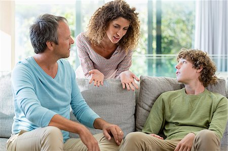 Happy family talking in a living room at home Stock Photo - Premium Royalty-Free, Code: 6108-08662777