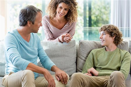 Happy family smiling in a living room at home Stock Photo - Premium Royalty-Free, Code: 6108-08662775
