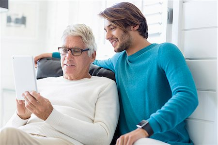 Happy father and son using digital tablet in living room Stock Photo - Premium Royalty-Free, Code: 6108-08663121