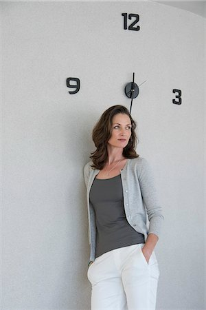 Beautiful woman leaning against a wall and thinking Stock Photo - Premium Royalty-Free, Code: 6108-08663313