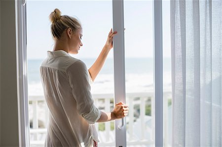 Young woman standing by window at home Stock Photo - Premium Royalty-Free, Code: 6108-08663402
