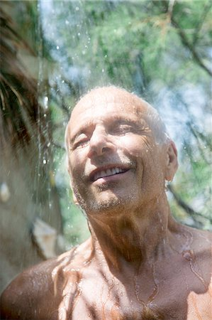 Close-up of smiling man taking a shower inside Stock Photo - Premium Royalty-Free, Code: 6108-08637047