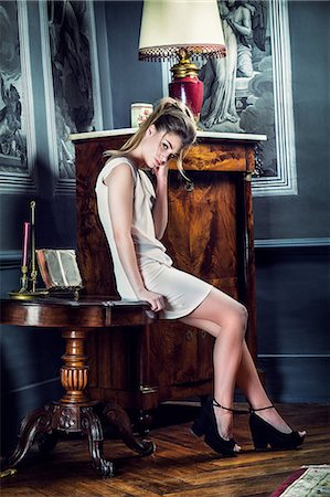 Young woman sitting on a table Stock Photo - Premium Royalty-Free, Code: 6108-08637077