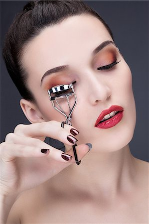 Portrait of a young woman using eyelash curler Stock Photo - Premium Royalty-Free, Code: 6108-08637320