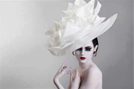 Portrait of a young woman wearing a face of luxury hat Stock Photo - Premium Royalty-Free, Code: 6108-08637405