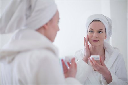 Woman in bathrobe using moisturizer in front of the mirror Stock Photo - Premium Royalty-Free, Code: 6108-08943567