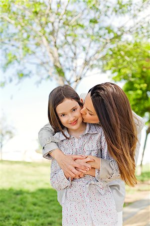 Mother kissing her daughter in the park Stock Photo - Premium Royalty-Free, Code: 6108-08909091