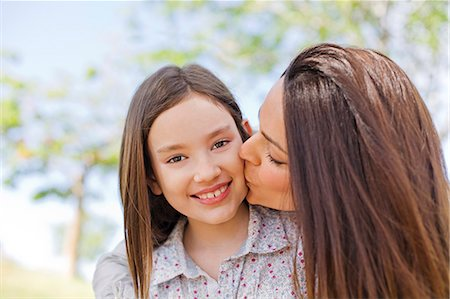 Mother kissing her daughter in the park Stock Photo - Premium Royalty-Free, Code: 6108-08909092