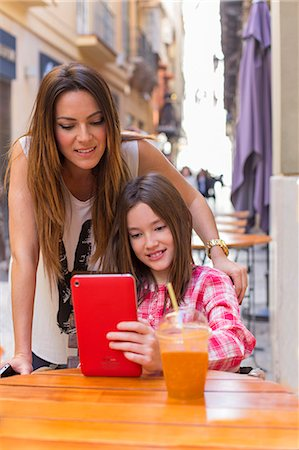 Mother and daughter with tablet in a Cafe Stock Photo - Premium Royalty-Free, Code: 6108-08909828