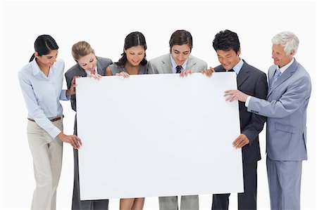 presentation (displaying) - Close-up of a multicultural business team holding a big white placard against white background Stock Photo - Premium Royalty-Free, Code: 6109-06002771