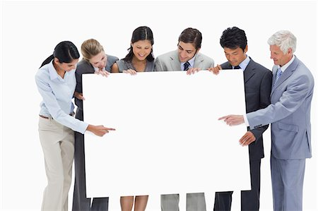 Close-up of a multicultural business team holding and showing a big placard white against white background Stock Photo - Premium Royalty-Free, Code: 6109-06002772