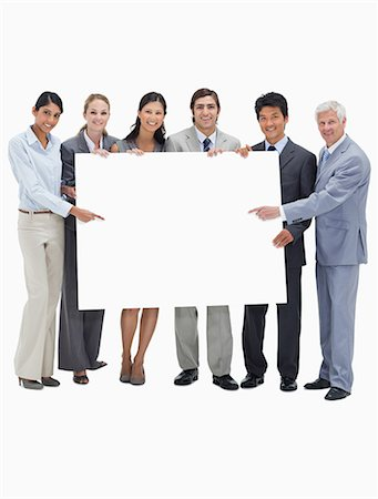 Smiling multicultural business team holding and showing a placard against white background Stock Photo - Premium Royalty-Free, Code: 6109-06002775