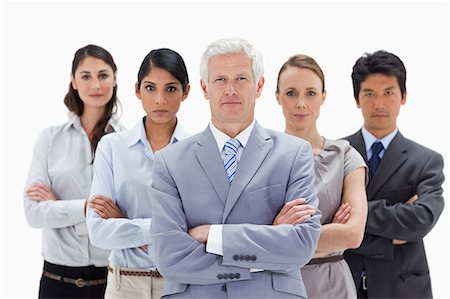 Close-up of a multicultural business team behind their boss against white background Stock Photo - Premium Royalty-Free, Code: 6109-06002702