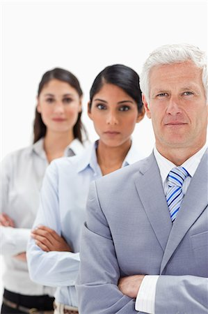 Close-up of a business man with two women behind him against white background Stock Photo - Premium Royalty-Free, Code: 6109-06002724