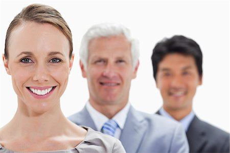 Close-up of smiling business people in a single line with focus on the woman against white background Stock Photo - Premium Royalty-Free, Code: 6109-06002735