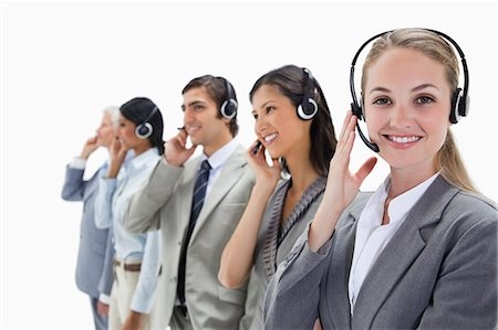 Smiling professionals listening with headsets against white background Stock Photo - Premium Royalty-Free, Code: 6109-06002811