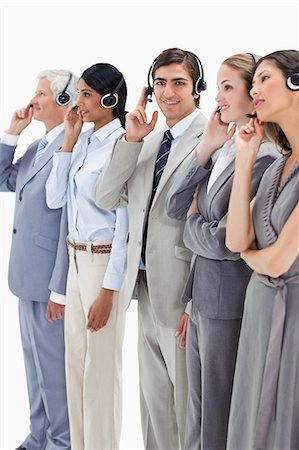 Professionals in suits listening with headsets against white background Stock Photo - Premium Royalty-Free, Code: 6109-06002820