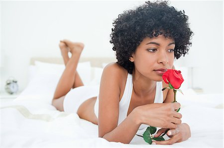 smelly - Black haired woman smelling a rose while lying on her bed Stock Photo - Premium Royalty-Free, Code: 6109-06002915