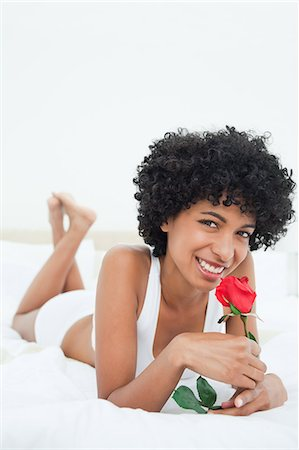 smelly - Portrait of a smiling black haired woman smelling a rose while lying on her bed Stock Photo - Premium Royalty-Free, Code: 6109-06002918