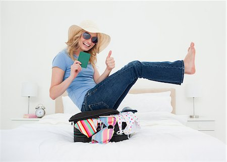 silhouette hand - A woman giving a thumbs up as she wears glasses and a hat, while balancing on top of her suitcase. Stock Photo - Premium Royalty-Free, Code: 6109-06003082