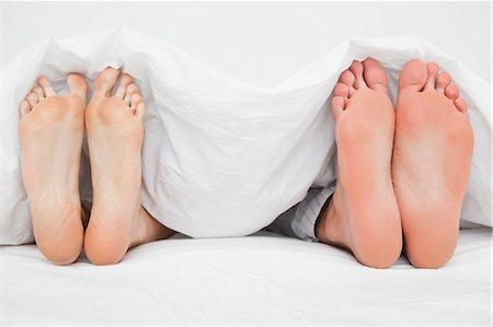 Two pairs of feet beside each other pointing straight up in the bed. Stock Photo - Premium Royalty-Free, Code: 6109-06003217