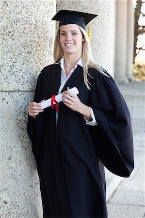Smiling graduating student standing upright with her diploma Stock Photo - Premium Royalty-Free, Code: 6109-06003566