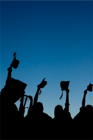 Young graduating students celebrating their new graduation while raising their caps Stock Photo - Premium Royalty-Free, Code: 6109-06003588