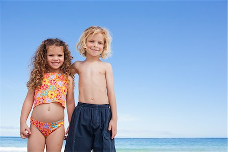 Young siblings standing arm in arm on the beach Stock Photo - Premium Royalty-Free, Code: 6109-06003666