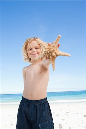 sea star - Smiling little boy on the beach with starfish Stock Photo - Premium Royalty-Free, Code: 6109-06003697