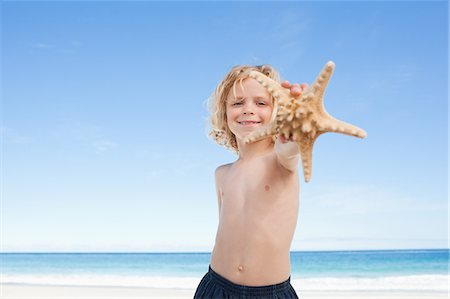 sea star - Cute little boy on the beach showing his starfish Stock Photo - Premium Royalty-Free, Code: 6109-06003698