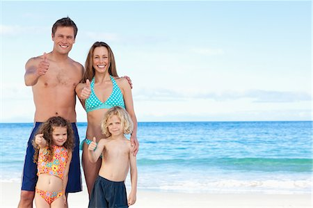Happy young family on the beach giving thumb up Stock Photo - Premium Royalty-Free, Code: 6109-06003617