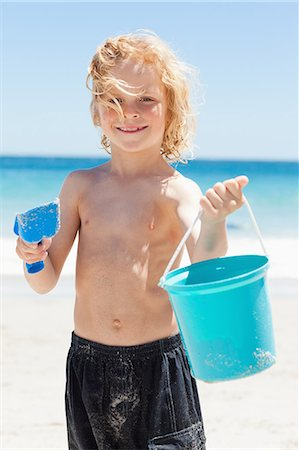 Smiling little boy with his bucket and shovel at the beach Stock Photo - Premium Royalty-Free, Code: 6109-06003779