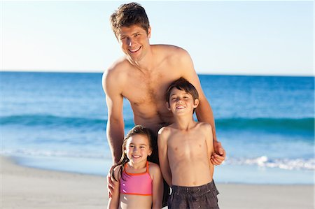 Smiling father standing with his little children on the beach Stock Photo - Premium Royalty-Free, Code: 6109-06003791