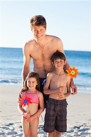 Smiling father on the beach together with his little children Stock Photo - Premium Royalty-Free, Code: 6109-06003792