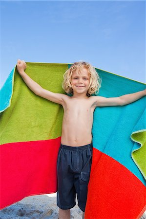 Little boy about to dry himself off on the beach Stock Photo - Premium Royalty-Free, Code: 6109-06003708