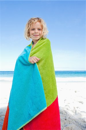 Smiling little boy on the beach wrapped into his towel Stock Photo - Premium Royalty-Free, Code: 6109-06003710