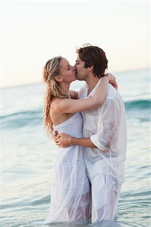 Side view of young couple standing in the sea while kissing Stock Photo - Premium Royalty-Free, Code: 6109-06003843