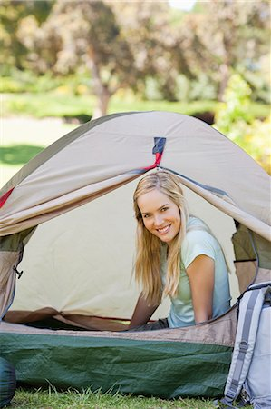 A woman almost fully inside a tent as she smiles with her head just outside the door of it Stock Photo - Premium Royalty-Free, Code: 6109-06003893