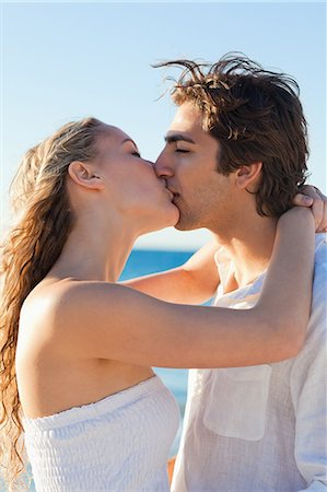 Side view of a kissing young couple at the beach Stock Photo - Premium Royalty-Free, Code: 6109-06003807