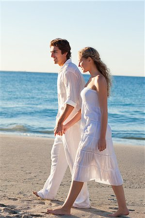 Side view of young couple walking at the seaside Stock Photo - Premium Royalty-Free, Code: 6109-06003835