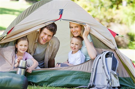 While camping the entire family smiles while sitting inside the tent Stock Photo - Premium Royalty-Free, Code: 6109-06003909
