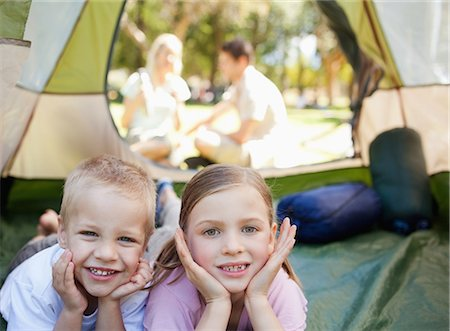 A pair of smiling kids lie down in the tent together with their parents outside Stock Photo - Premium Royalty-Free, Code: 6109-06003913