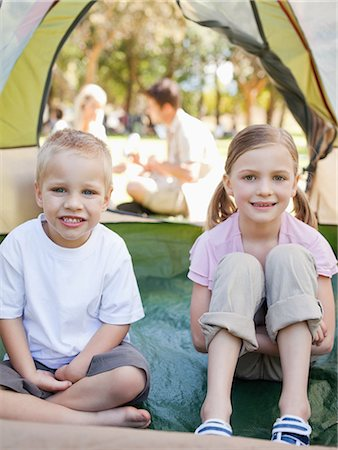 A smiling brother and sister sit inside of the tent as their parents sit outside talking Stock Photo - Premium Royalty-Free, Code: 6109-06003911